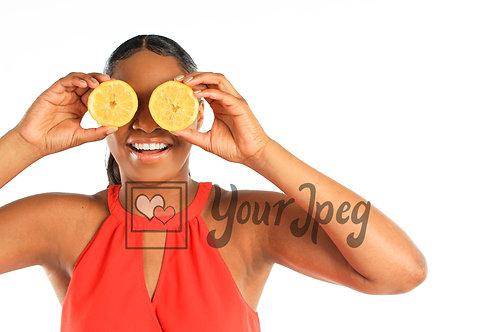 Woman holding lemons to eyes