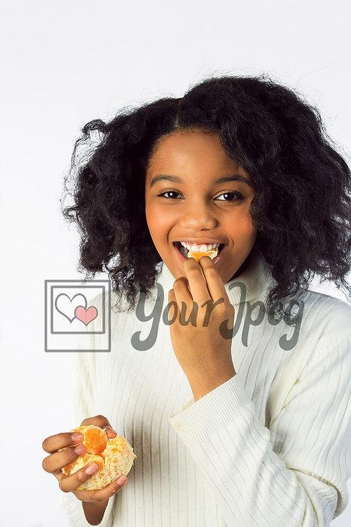 Tween girl eating orange