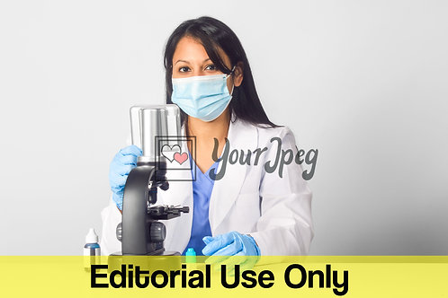 Female Doctor Wearing Mask And Gloves While Using Microscope #1