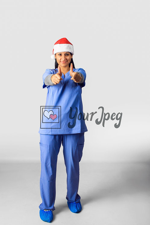 Female Nurse Wearing Christmas Hat With Thumbs Up