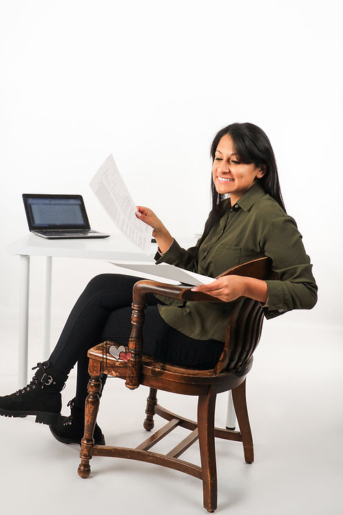 Woman Smiling At Computer Desk Holding Paper