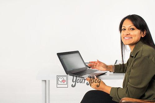 Woman Sitting At Desk Using Laptop Smiling