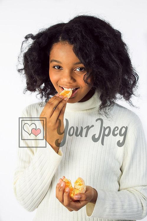 Tween girl smiling biting orange