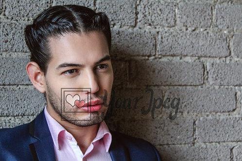 Headshot of man against brick wall.