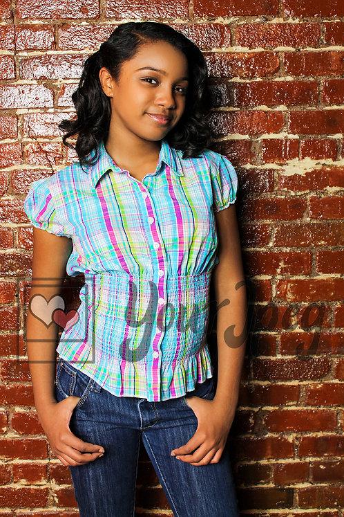 Tween girl leaning against brick wall 2