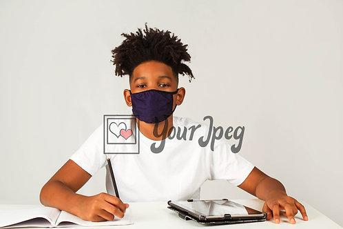Boy wearing mask sitting at desk
