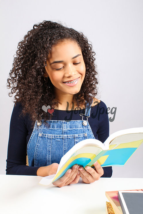 Teenage Girl Smiling While Reading Book
