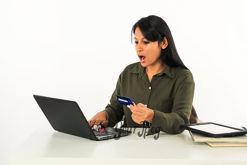 Woman Holding Credit Card While Looking At Laptop Surprised