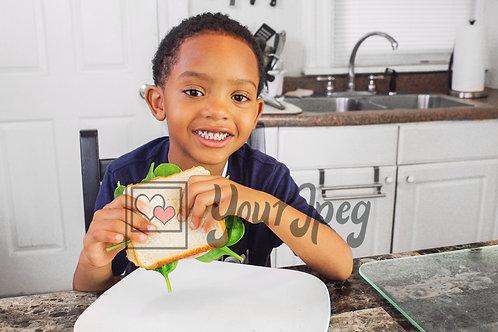 Boy smiling holding sandwich 1