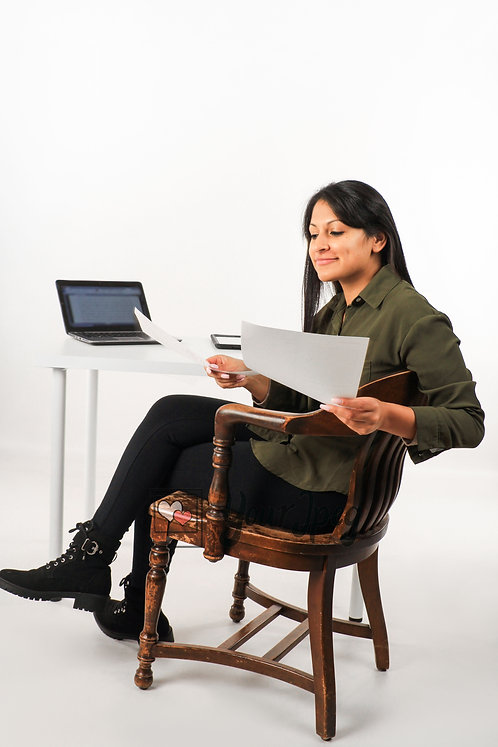 Woman Sitting At Computer Desk Holding Paper