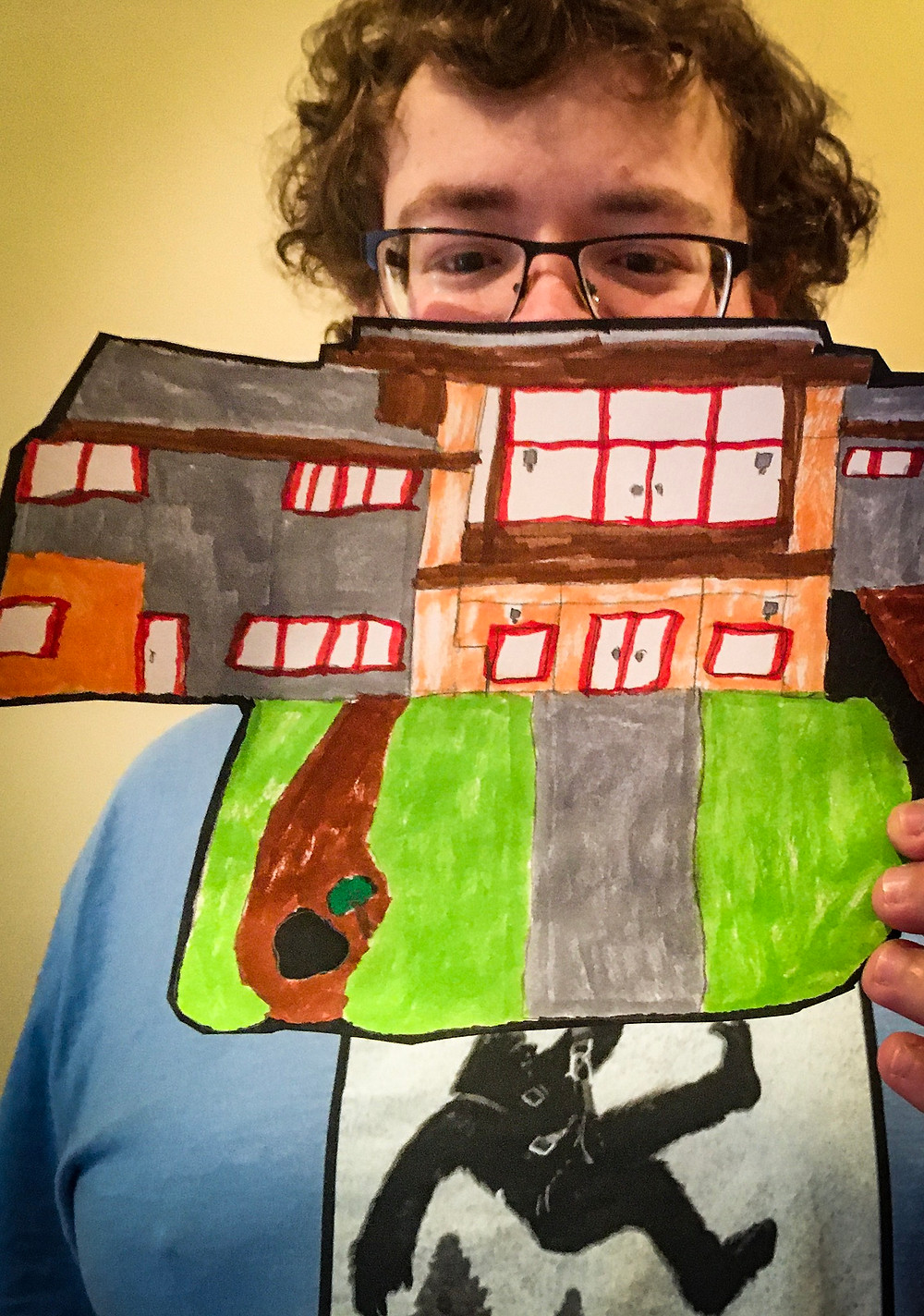 A young man who experiences a developmental disability holds up a picture he drew of his Adult Family Home