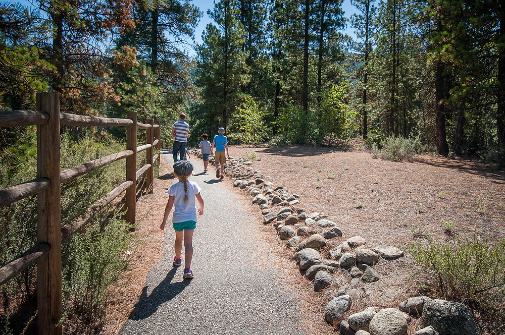 A family walks on paved, wheel chair accessible hiking trail at the Leavenworth Fish Hatchery, Leavenowrth, WA
