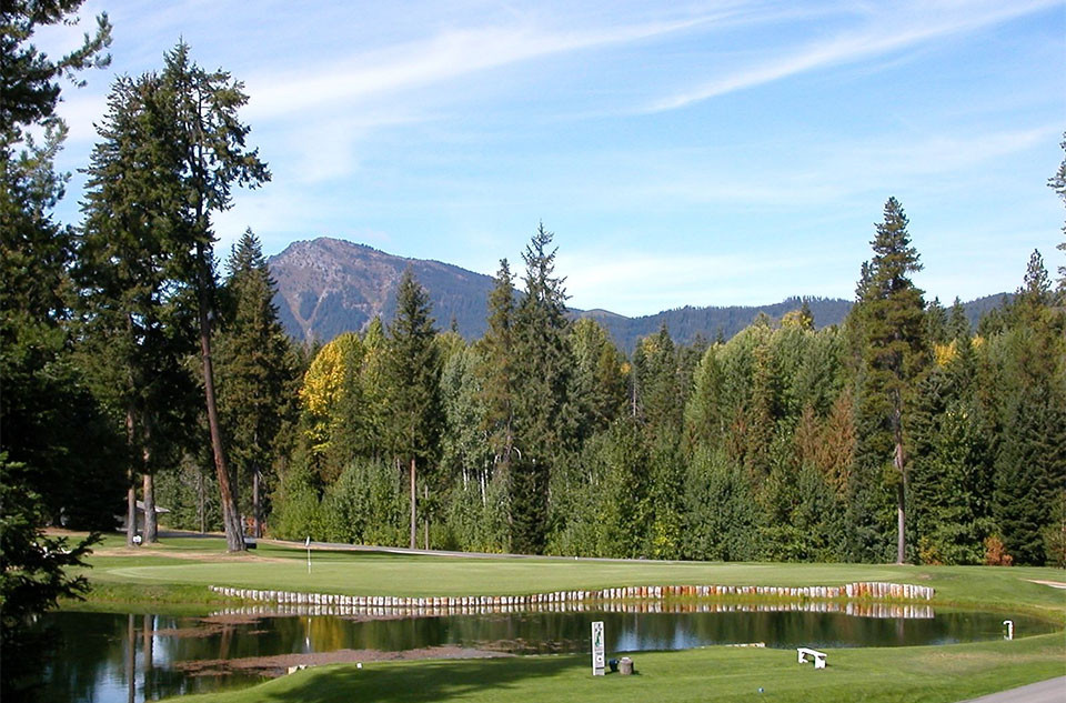 A view of a pond, golf course, forest, and wheel-chair accessible hiking path at Kaylor Glen, located outside Leavneoworth, WA, near Lake Wenatchee