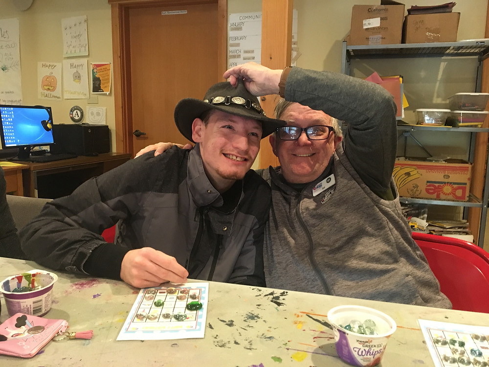 Ed Harris, an AmeriCorps Volunteer for Tierra Village, puts his cowboy hat on a participants head in TRAILS Day Program.