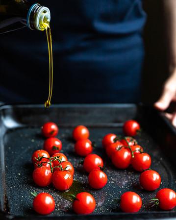 Woman pouring Olive oil over Vine Tomato