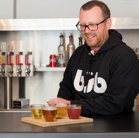 Man looking at 4 small glasses of beer on a tray_Bitte Schon Brewery _Restaurant Photograp