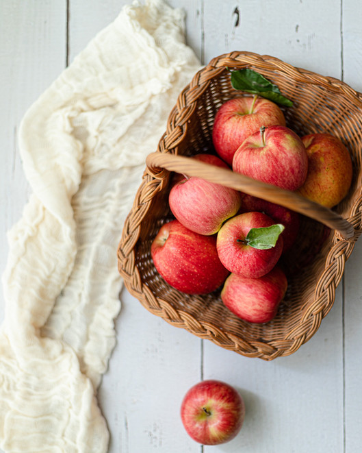 Apples in straw basket on white table_Food Photography_Bonjour Tasty by Florence Grunfelde