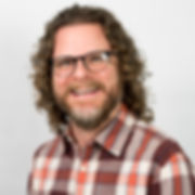 Pic of Loren Pilcher, Director of Community Supports. Man in thirties with brown hair, beard, and glasses.