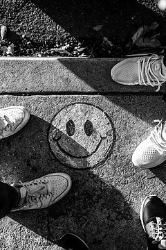 smiley%20paint%20on%20gray%20ground%20in%20front%20of%20people_edited.jpg