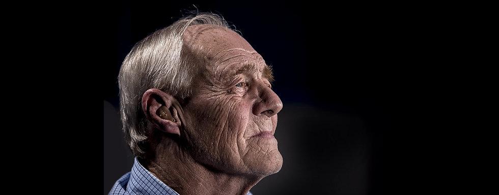 Senior op leeftijd kijkt mijmerend voor zich uit.