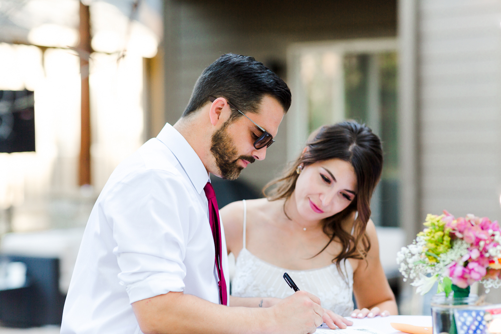 Groom signing marriage certificate during Sunriver Oregon wedding