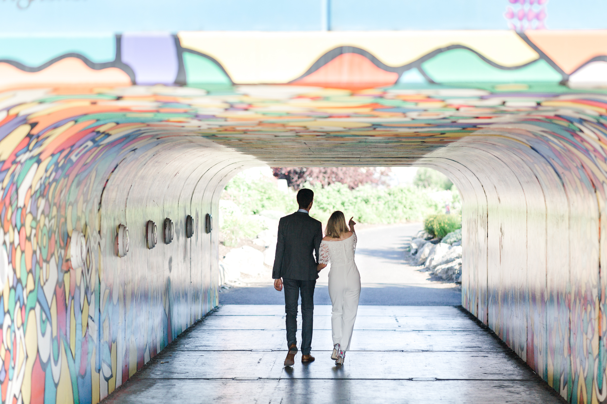Bride and groom walking through painted tunnel in Bend oregon Old Mill District