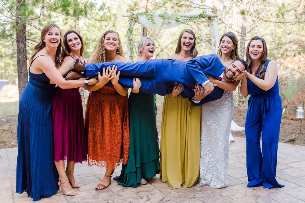 Bridesmaids lifting groom during Sunriver Oregon wedding