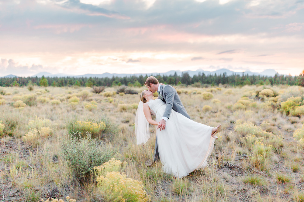 Bride and groom dip kiss in Shevlin Park at Sunset
