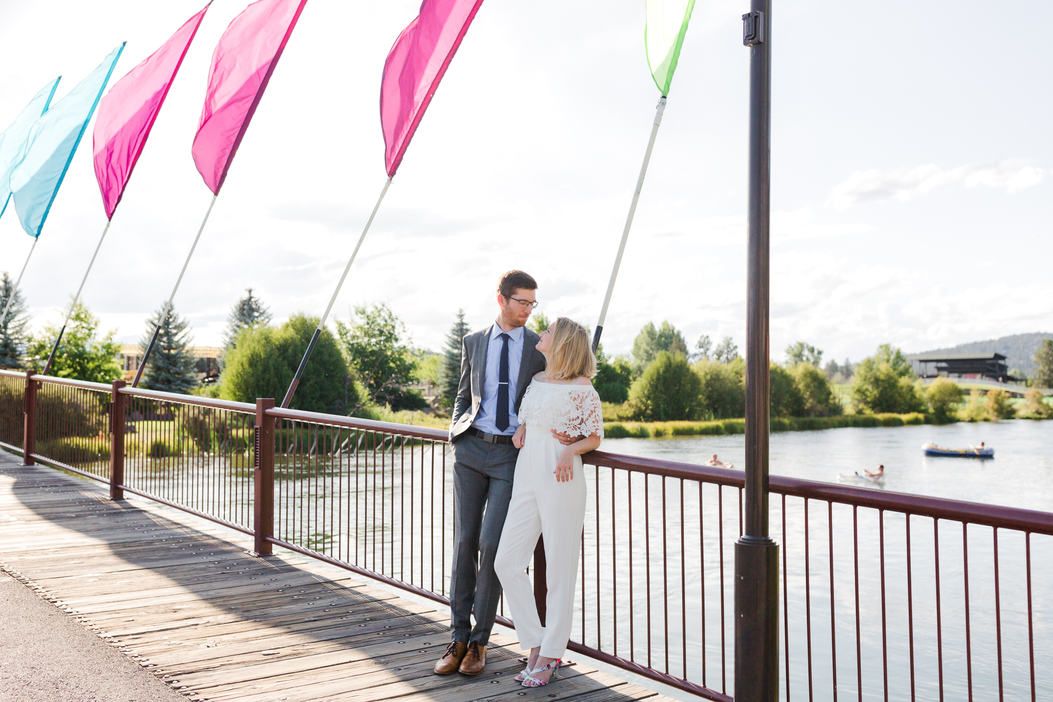 Bride in jumpsuit and groom on Old Mill District bridge