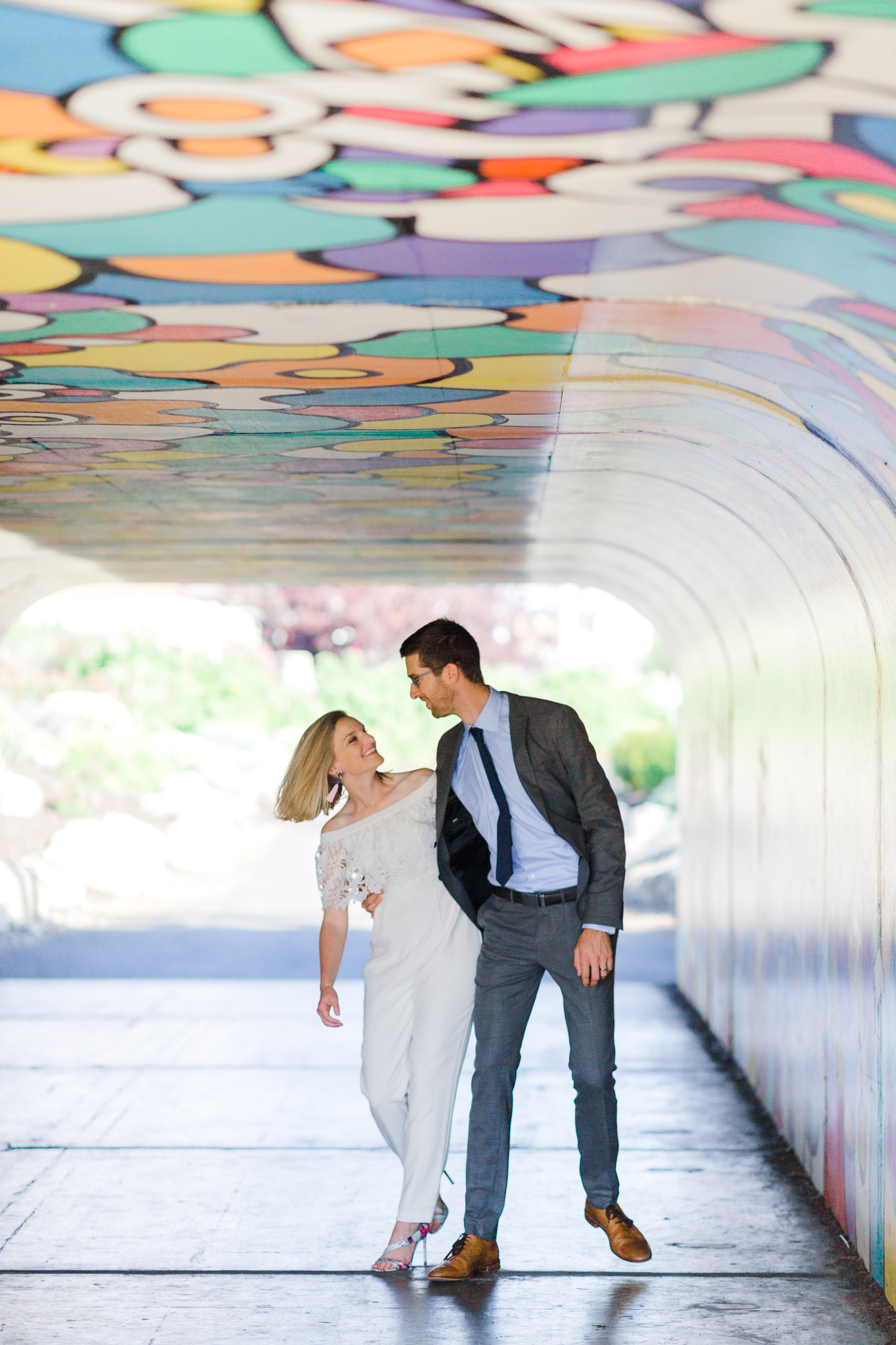 Bride and groom walking in Old Mill District tunnel
