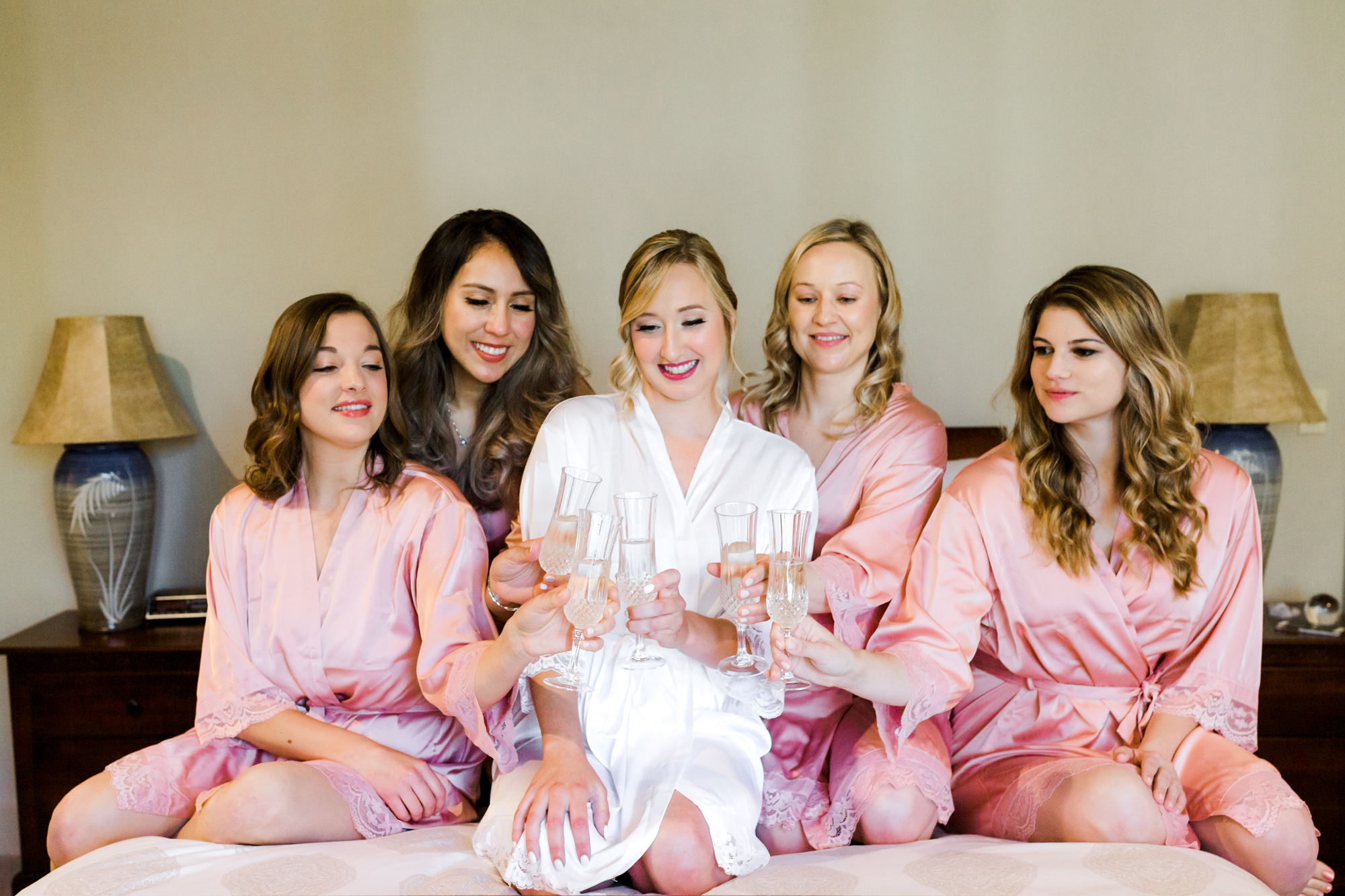 Bride and bridesmaid cheers on bed in Bend Oregon