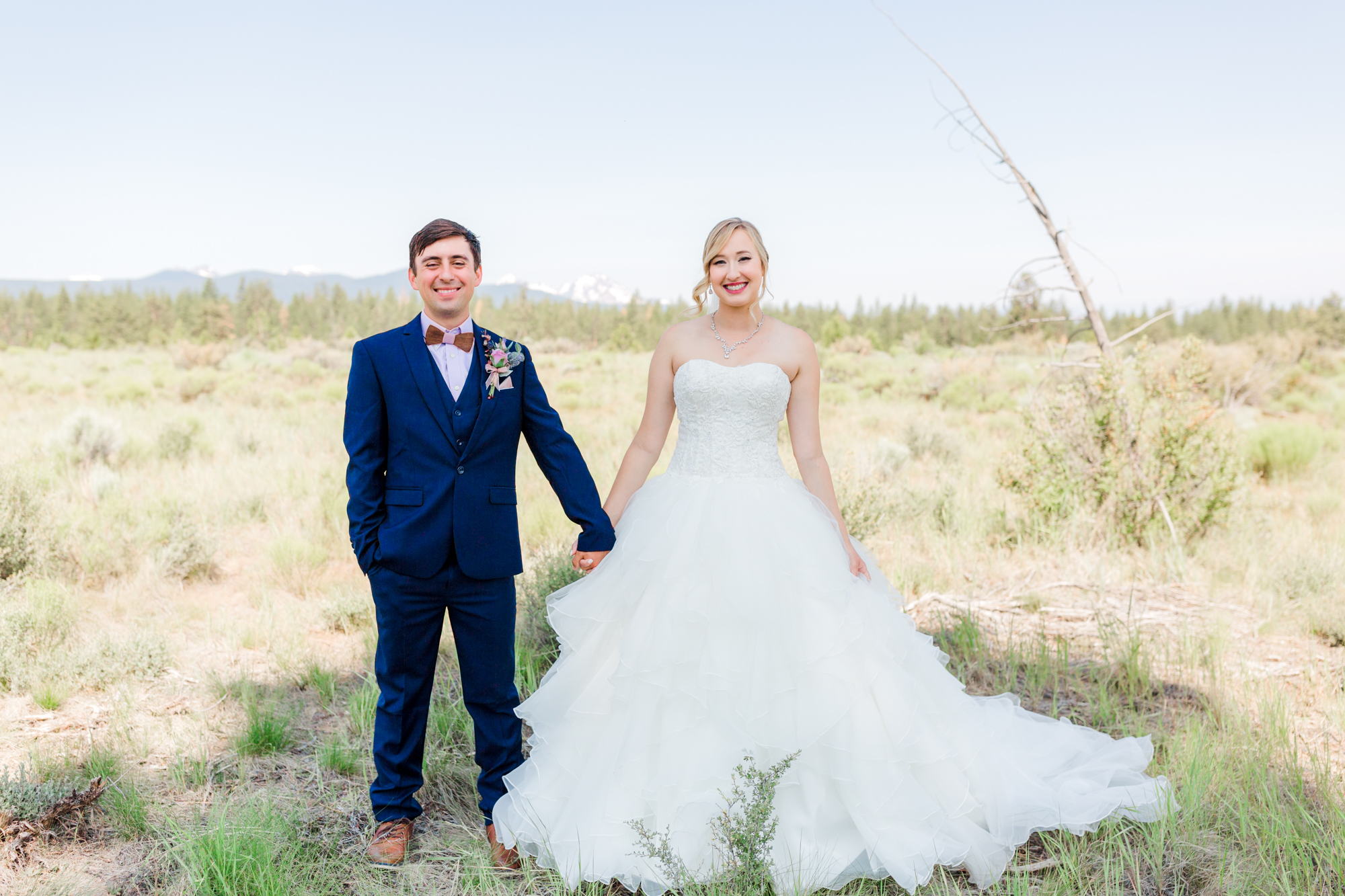 Bride and groom stand hand in hand at Upper Shevlin Park in Bend Oregon