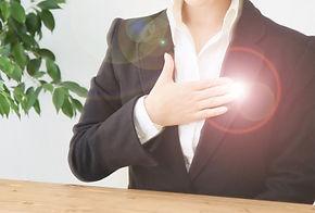 手を胸に当てるスーツの女性
