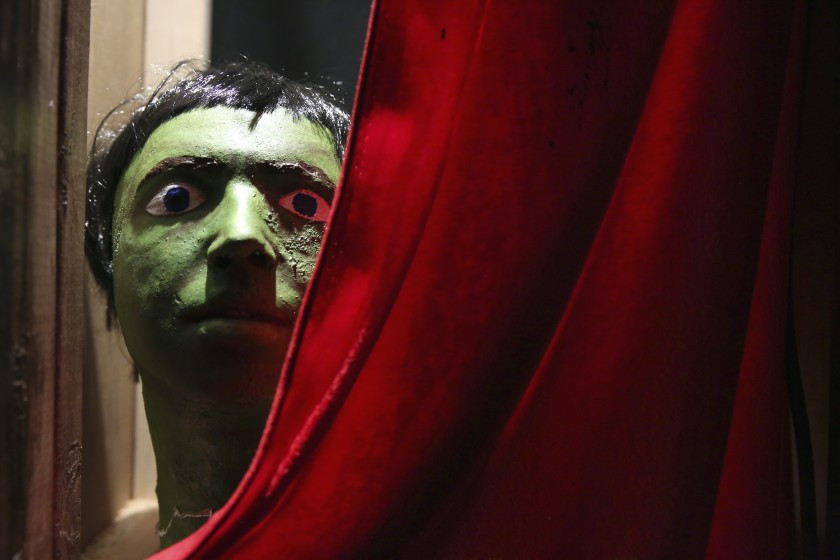 Face in a green cracked mask with painted eyes peering from red curtain