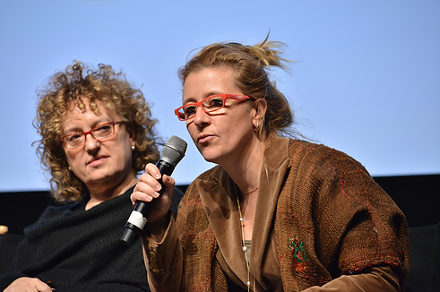 a person speaking into microphone and another listens