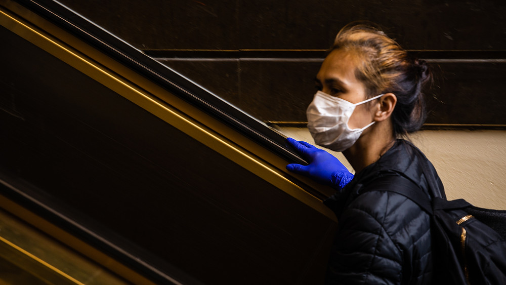woman in surgical mask and gloves on escalator