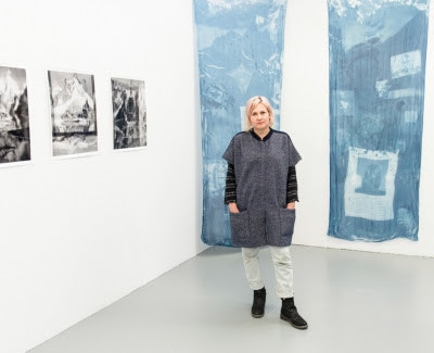 Image of artist standing in front of their work