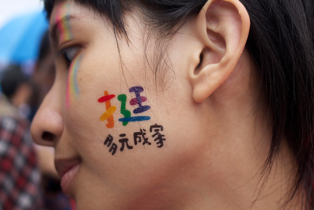 "A woman with a temporary tattoo on her cheek, reading ""Support diverse families"" in Chinese."