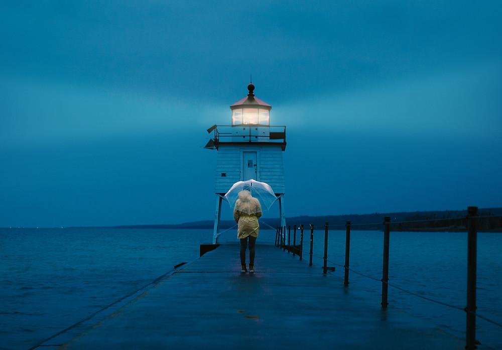 woman on peer with umbrella