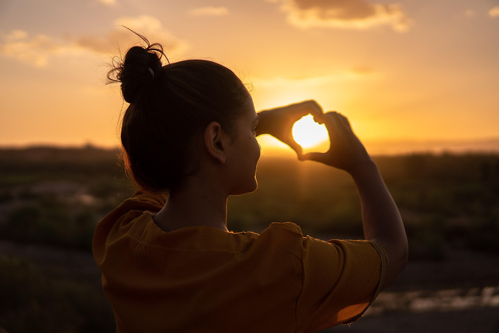 woman at sunrise making heart with hand