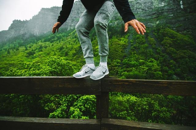 man standing on fence, balancing
