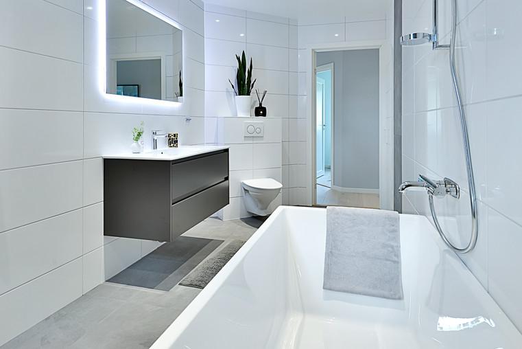 badrum med badkar och vitt kakel renovering gjord i kungsängen