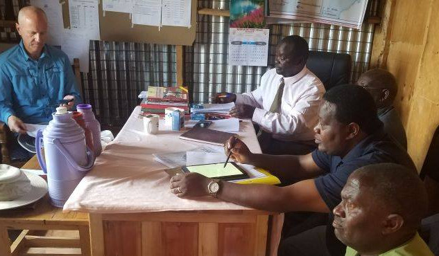 Tom, LSS principal, Chrm of LSS Management Board, Charles and Vice-Chrm of LSS Management Board look over the history, values, and vision of Lamuria Secondary School.