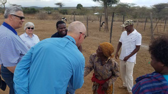 Pastor Stephen's mom offers Tom and Mitch a calf and greets with a handshake.