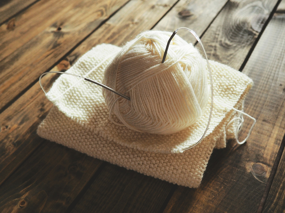 knitting needles through a ball of white wool yarn, on top of a white wool scarf