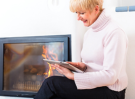 Woman enjoying a natural gas fireplace