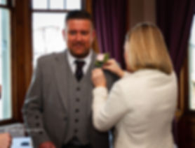 groom getting corsage put on