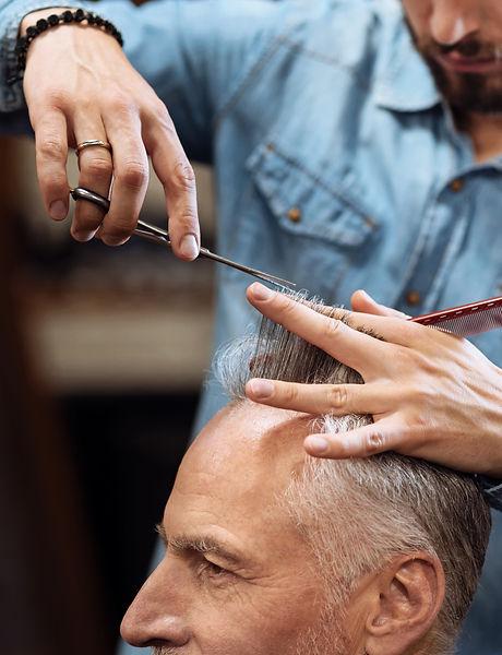 closeup-of-senior-man-having-haircut-in-