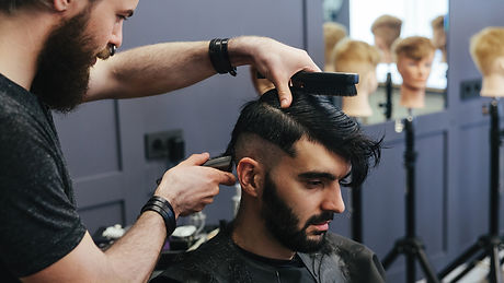 male-barber-combing-and-shaving-hair-of-