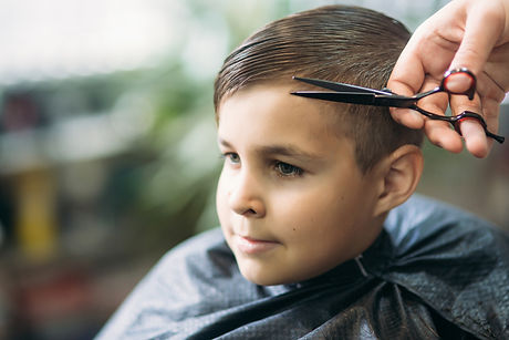 little-boy-getting-haircut-by-barber-whi